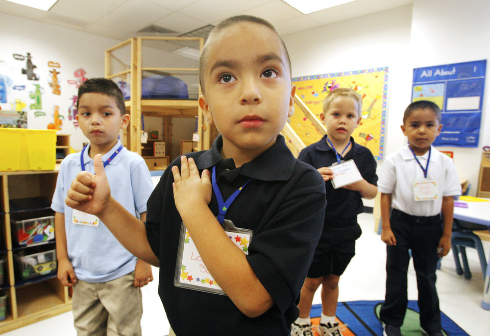 Photo - Prekindergarten student Erik Lopez-Servin, 4, recites the Pledge of Allegiance at Adams Elementary on Aug. 1 as the new school year began.  Photo by Paul B. Southerland, The Oklahoman