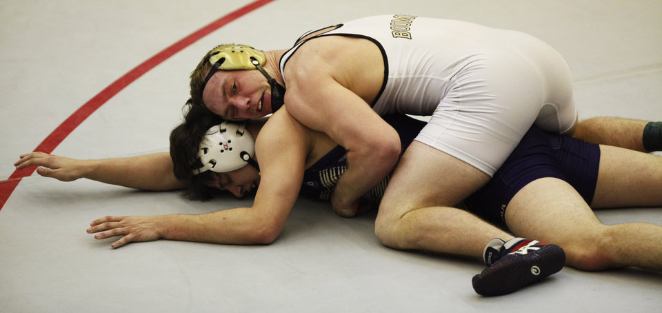 Photo - Anadarko's Tristan East (purple) and Woodward's Kyler Ferguson (white) wrestle in the 182 pound match at the 4A West Regional wrestling championship in Harrah on Saturday, Feb. 22, 2014. Woodward's Kyler Ferguson defeated Anadarko's Tristan East to advance to state. Photo by KT King, The Oklahoman