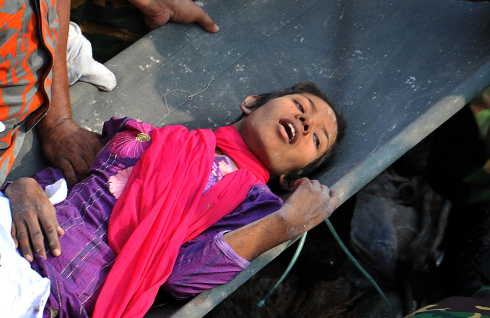 Photo - A survivor lies on a stretcher after being pulled out from the rubble of a building that collapsed in Savar, near Dhaka, Bangladesh, Friday, May 10, 2013. Rescue workers in Bangladesh freed the woman buried for 17 days inside the wreckage of a garment factory building that collapsed, killing more than 1,000 people. Soldiers at the site said her name was Reshma and described her as being in remarkably good shape despite her ordeal. (AP Photo)