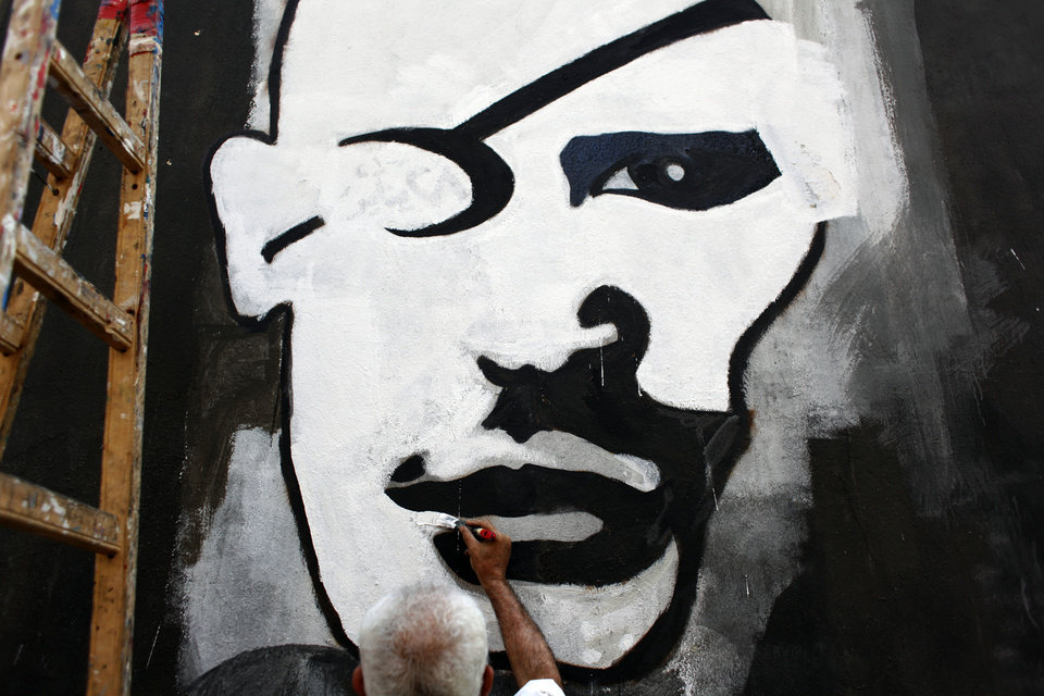 Photo -   FILE - In this Sunday. Sept. 30, 2012 file photo, an Egyptian activist artist works on a mural depicting a rebel with an eye patch in Tahrir square, Cairo, Egypt. Graffiti has been among the most powerful art forms and tools of Egypt's revolution and the turbulent months since, but it also has proven to be its most vulnerable and ephemeral. So a group of artists, photographers and a publisher joined hands to preserve the images.