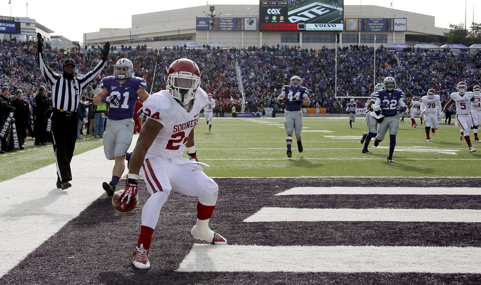 Oklahoma's Brennan Clay (24) sets the ball down after scoring on a 64-yard touchdown run during an NCAA college football game between the Oklahoma Sooners and the Kansas State University Wildcats at Bill Snyder Family Stadium in Manhattan, Kan., Saturday, Nov. 23, 2013. Photo by Bryan Terry, The Oklahoman