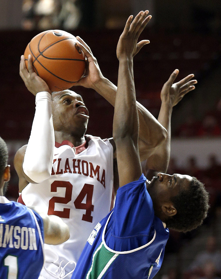 Photo - Oklahoma's Buddy Hield (24) shoots a lay up as Texas A&M-CC's Hameed Ali (1) defends during the men's college game between the University of Oklahoma and the Texas A & M- Corpus Christi at Lloyd Noble Center in Norman, Okla.,  Thursday, Dec. 5, 2013. Photo by Sarah Phipps, The Oklahoman