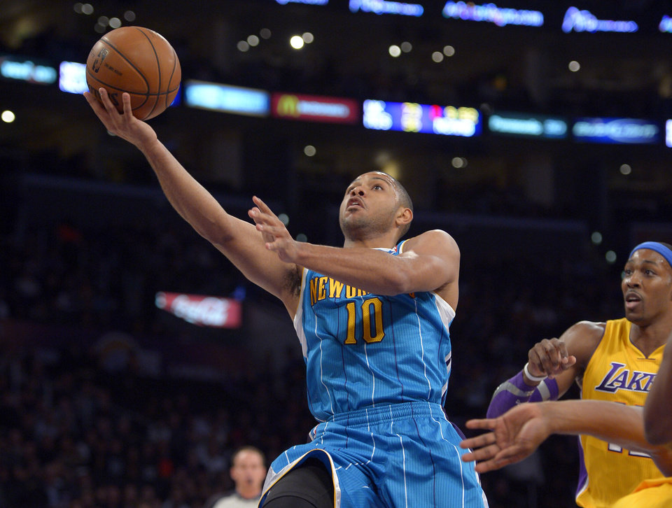 New Orleans Hornets guard Eric Gordon puts up a shot as Los Angeles Lakers center Dwight Howard watches during the first half of an NBA basketball game, Tuesday, Jan. 29, 2013, in Los Angeles. (AP Photo/Mark J. Terrill)