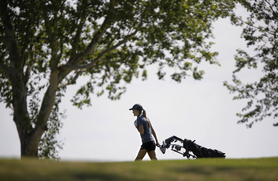 Photo - A golfer pulls her clubs across the course during the 2014 Class 2A girls' golf state championship tournament  Wednesday, May 7, 2014, at Trosper Golf Course in Del City.  Photo by Jim Beckel, The Oklahoman