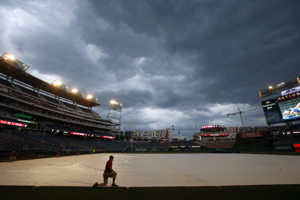Photo - A member of the grounds crew kneels on the tarp during a rain delayed start of an interleague baseball game between the Washington Nationals and the Baltimore Orioles at Nationals Park, Tuesday, July 8, 2014, in Washington. (AP Photo/Alex Brandon)