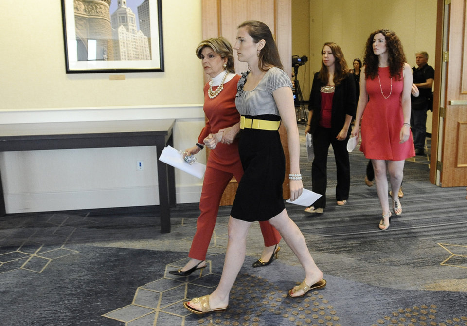 Photo - Attorney Gloria Allred, left center, leaves a news conference with Kylie Angell, center, Erica Daniels, second from right, and Rosemary Richi, right, Friday, July 18, 2014, in Hartford, Conn.  The University of Connecticut will pay nearly $1.3 million to settle a federal lawsuit filed by five women who claimed the school responded to their sexual assault complaints with indifference, the two sides announced Friday.  (AP Photo/Jessica Hill)