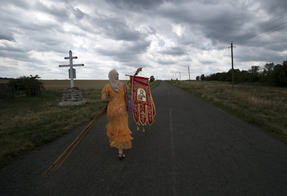 Photo - A woman carries icons before a religious service held by villagers in memory of the victims at the crash site of Malaysia Airlines Flight 17, near the village of Hrabove, eastern Ukraine, Tuesday, July 22, 2014. A team of Malaysian investigators visited the site along with members of the OSCE mission in Ukraine for the first time since the air crash last week.(AP Photo/Vadim Ghirda)