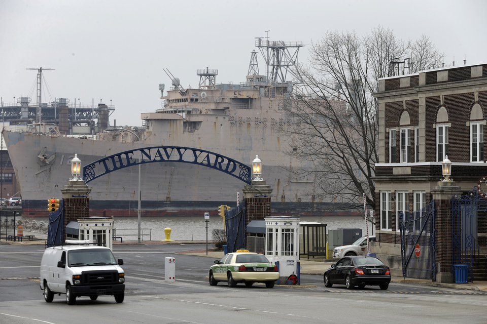 Photo - In this Wednesday, Feb. 6, 2013 photo, vehicles move thought the main gate at the Navy yard in Philadelphia. The city's Navy Yard is celebrating a milestone that skeptics might not have believed 15 years ago. Nearly all naval operations are long gone from the sprawling former shipyard but 10,000 people now work there in an eclectic mix of businesses from fashion to pharmacies. That number is expected to triple in 20 years. (AP Photo/Matt Rourke)