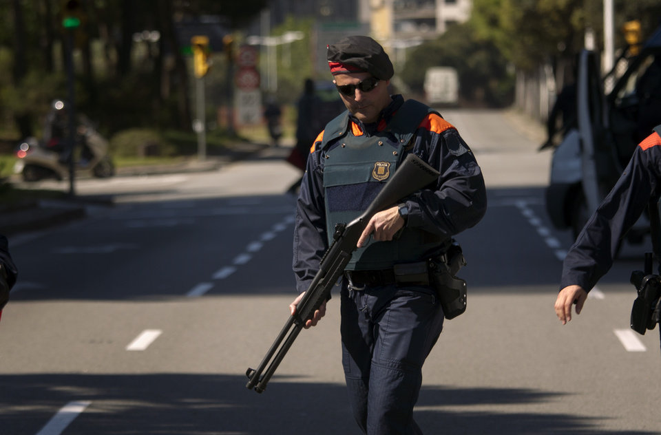 Photo -   A police officer holds a weapon in a checkpoint near the hotel where the meeting of the European Central Bank is taking place in Barcelona, Spain, Thursday, May 3, 2012. European stocks pushed ahead Thursday after cash-strapped Spain got through another set of bond auctions unscathed and ahead of the latest policy statement from the European Central Bank's president Mario Draghi. (AP Photo/Emilio Morenatti)