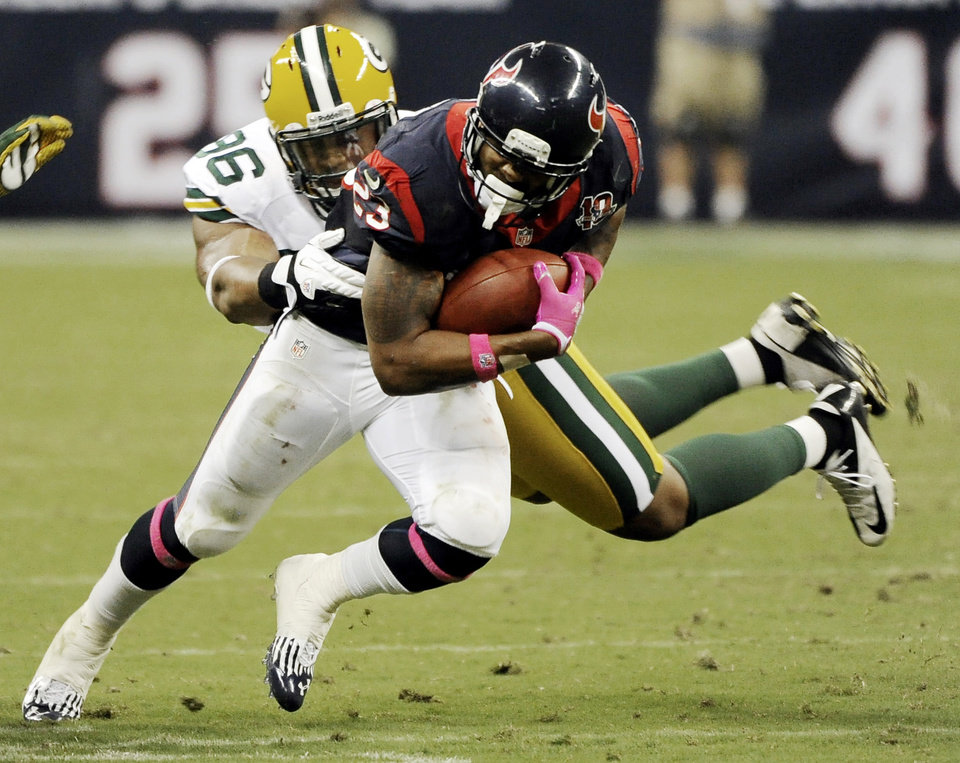Houston Texans running back Arian Foster (23) is tackled by Green Bay Packers defensive tackle Mike Neal (96) in the second quarter of an NFL football game, Sunday, Oct. 14, 2012, in Houston. (AP Photo/Dave Einsel)