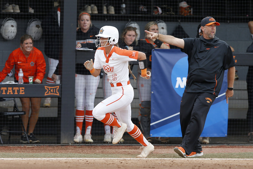 Photo - Oklahoma State's Kiley Naomi (5) runs homes to score past Oklahoma State coach Kenny Gajewski in the fourth inning of the Stillwater Regional NCAA softball tournament game between Oklahoma State University (OSU) and Tulsa in Stillwater, Okla., Saturday, May 18, 2019. Oklahoma State won 2-1. [Bryan Terry/The Oklahoman]