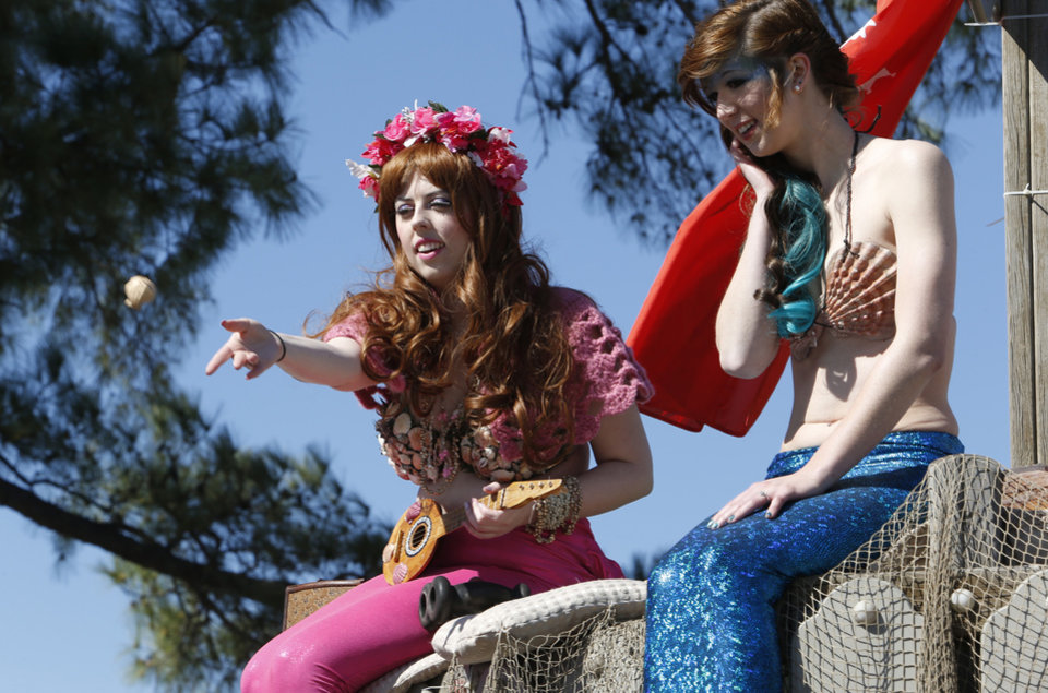 Photo -  Mermaid Neolani throws gifts to the crowd as Merida watches at the Medieval Fair Friday at Reaves Park in Norman. PHOTO BY STEVE SISNEY, THE OKLAHOMAN   STEVE SISNEY -