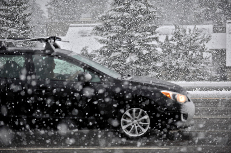 Photo - A driver travels west on I-70 during a snowstorm in Vail, Colo. on Sunday, May 11, 2014. The Mother's Day storm caused numerous accidents along the Interstate from Silverthorne to Gypsum. (AP Photo/Vail Daily, Anthony Thornton)