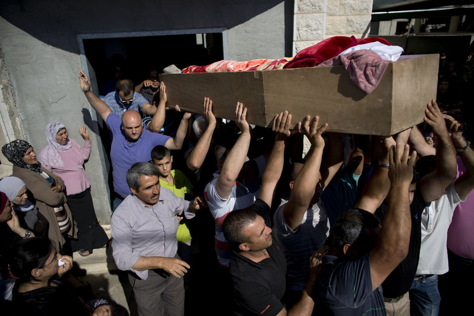 Photo - Relatives of Mohammed Krakra, an Israeli Arab teen, carry his coffin during his funeral at the northern Israeli Arab village of Arabeh, Israel, Monday, June 23, 2014. Israeli warplanes bombed the Syrian military headquarters and a number of other targets inside Syria, the Israeli military said Monday, in a blistering response to a cross-border attack that killed Krakra the previous day. (AP Photo/Oded Balilty)