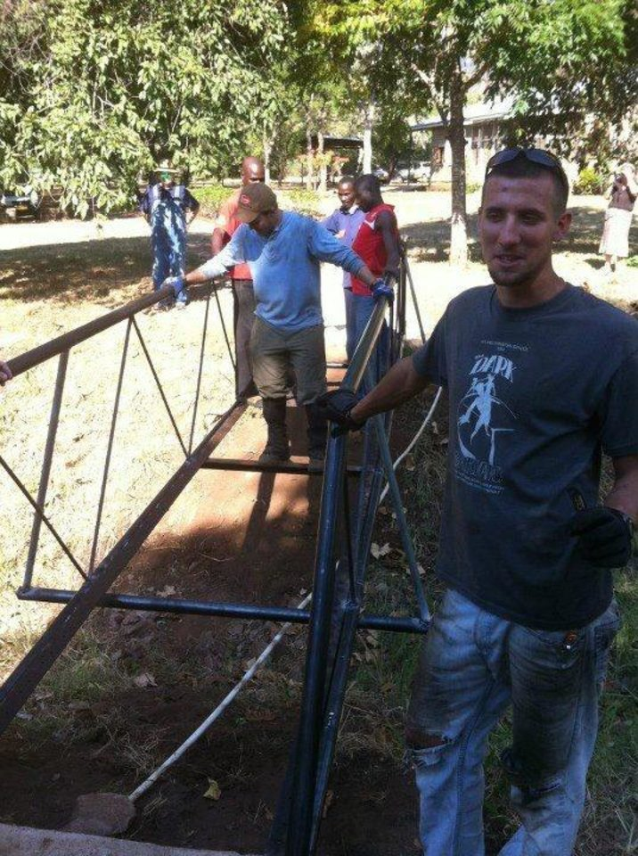Oklahoma Christian University student Nick Poulos, at right, stands next to the metal frame of a bridge he designed and helped build in Tanzania, Africa, during a summer mission trip. Photo provided <strong></strong>
