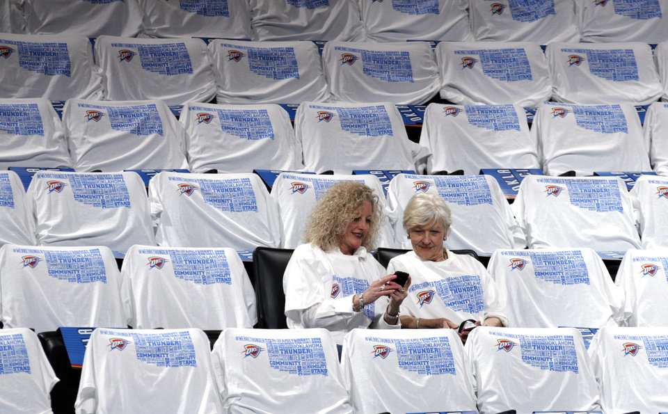 Photo - Machele McNeil, left and Barbara Pirkle look at a picture they tool of themselves during Game 5 in the first round of the NBA playoffs between the Oklahoma City Thunder and the Memphis Grizzlies at Chesapeake Energy Arena in Oklahoma City, Tuesday, April 29, 2014. Photo by Sarah Phipps, The Oklahoman