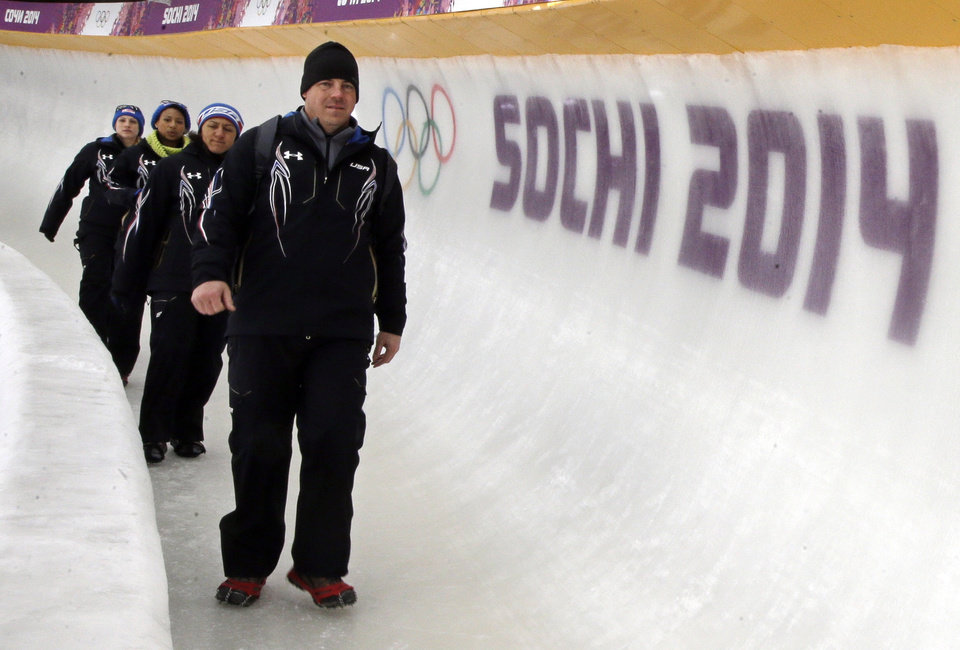 Photo - Todd Hays, right, coach of the United States women's team, walks the track with drivers Elena Meyers, left, Jazmine Fenlator, and Jamie Greubel, before a training run for the women's two-man bobsled at the 2014 Winter Olympics, Wednesday, Feb. 5, 2014, in Krasnaya Polyana, Russia. (AP Photo/Dita Alangkara)