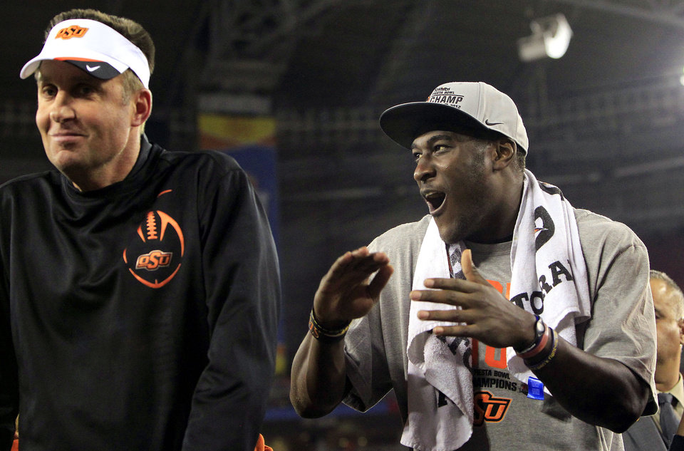 Photo - Oklahoma State head coach Mike Gundy, left, dances much to the delight of Justin Blackmon after the Fiesta Bowl NCAA college football game against Stanford Monday, Jan. 2, 2012, in Glendale, Ariz.  Oklahoma State defeated Stanford 41-38 in overtime.(AP Photo/Ross D. Franklin) ORG XMIT: PNP155