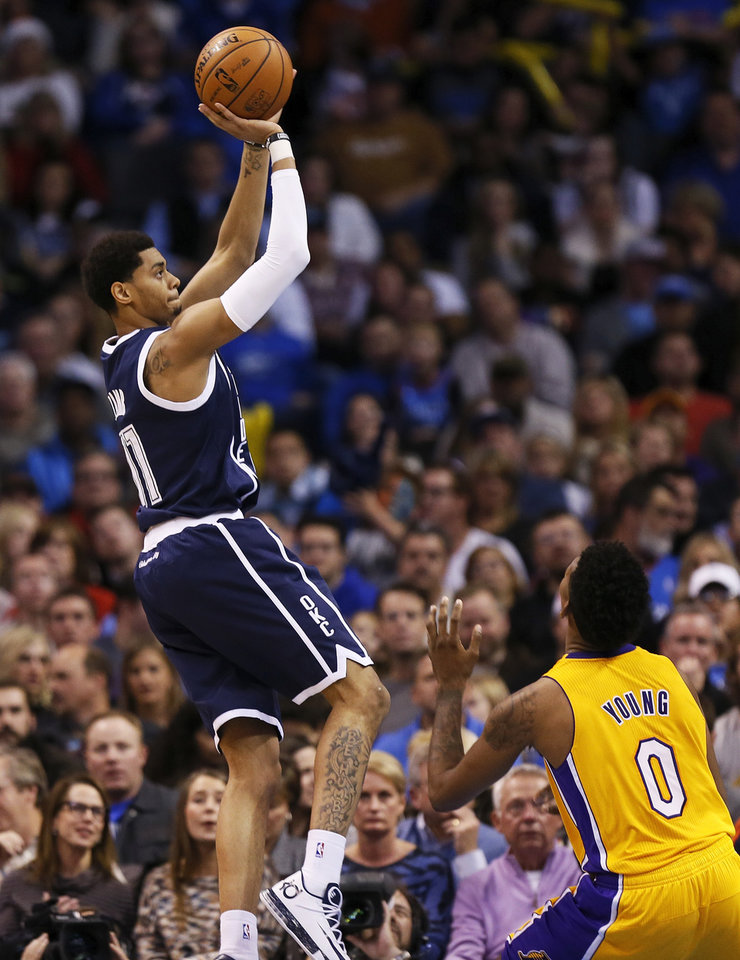 Photo - Oklahoma City's Jeremy Lamb (11) shoots over LA's Nick Young (0) during an NBA basketball game between the Los Angeles Lakers and the Oklahoma City Thunder at Chesapeake Energy Arena in Oklahoma City, Friday, Dec. 13, 2013. OKC won, 122-97. Photo by Nate Billings, The Oklahoman