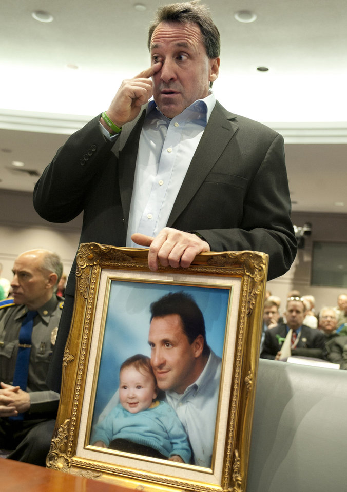 FILE - In a Jan. 28, 2013 file photo Neil Heslin, holds a picture of himself with his son Jesse and wipes his eye before testifying at a hearing in the Legislative Office Building in Hartford, Conn., Heslin will testify to the Senate Judiciary Committee Wednesday Feb. 27, 2013. (AP Photo/Jessica Hill)