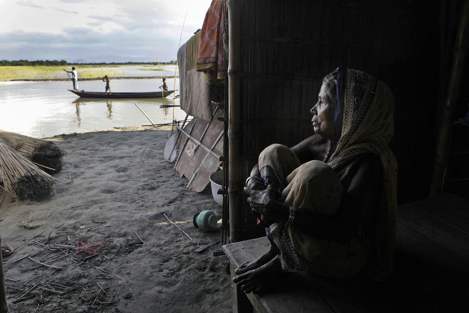 Photo -   Indian woman Anowara Bewa, 65, sits inside a makeshift temporary hut in the flood affected Gagalmari village in Assam state, India, Monday, July 2, 2012. The floods from monsoon rains in northeastern India killed dozens of people, with more than 2,000 villages inundated as rivers breached their banks, an official said Sunday. (AP Photo/Anupam Nath)