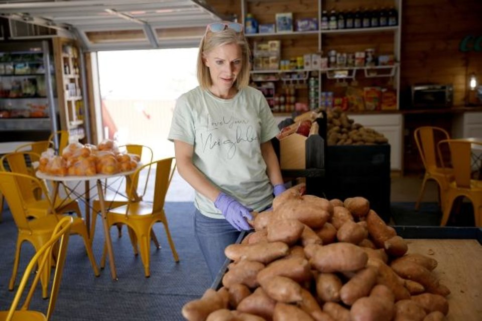 Photo - Kristen Hannam with Restore OKC stacks sweet potatoes inside The Market at Restore OKC in Oklahoma City, Thursday, March 26, 2020. [Bryan Terry/The Oklahoman]