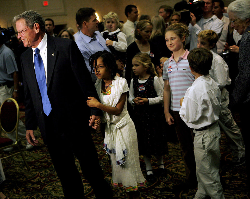Photo - Senator Jim Inhofe, followed by his grand children, including Marie Rapert (holding hands) greets supporters during the Republican watch party at the Oklahoma City Marriott on Northwest Expressway in oklahoma City on Tuesday Nov. 4, 2008. By John Clanton, The Oklahoman