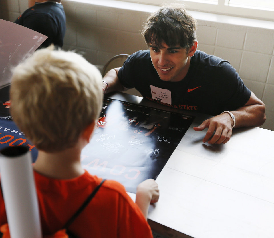 Photo - Oklahoma State quarterback Clint Chelf, right, talks with fan Corbin Ellis, 7, of Tulsa, during OSU Fan Appreciation Day at Gallagher-Iba Arena in Stillwater, Okla., Saturday, Aug. 4, 2012. Photo by Nate Billings, The Oklahoman