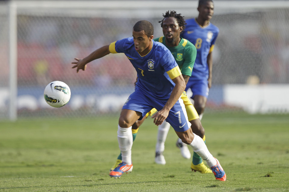 Photo -   Brazil's Lucas, front, fights for the ball with South Africa's Chabangu during a friendly soccer match in Sao Paulo, Brazil, Friday, Sept. 7, 2012. (AP Photo/Nelson Antoine)