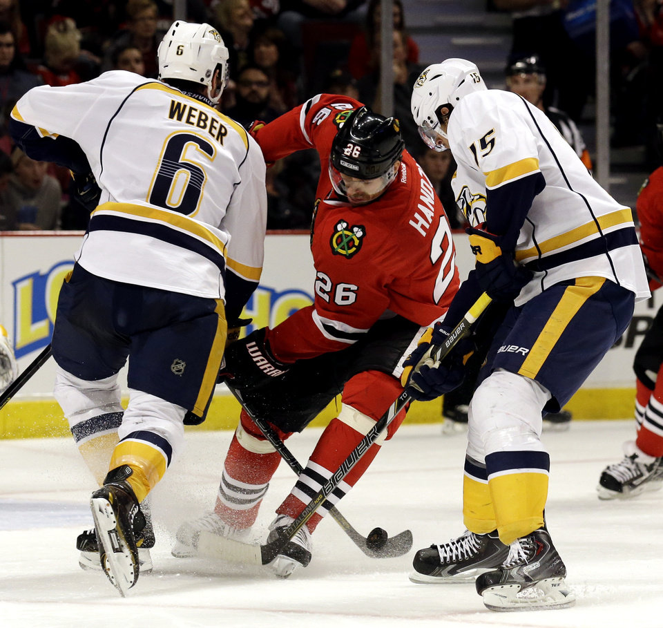 Photo - Chicago Blackhawks' Michal Handzus (26), center,  battles for the puck against Nashville Predators' Shea Weber (6), left, and Craig Smith (15) during the second period of an NHL hockey game in Chicago, Sunday, March 23, 2014. (AP Photo/Nam Y. Huh)
