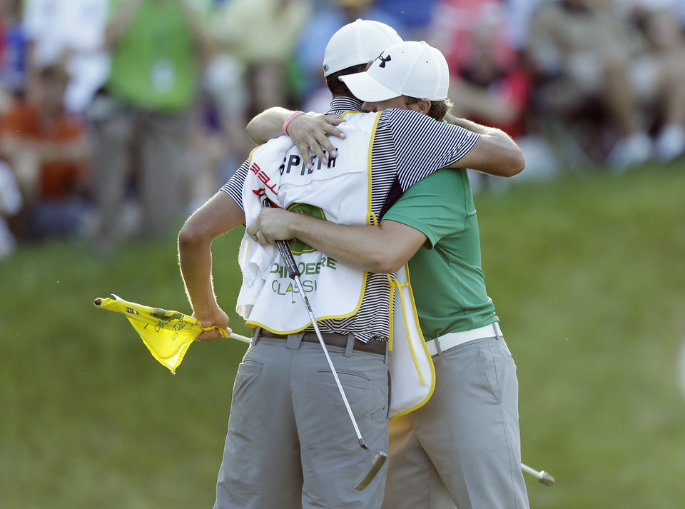 Photo - Jordan Spieth hugs his caddie Michael Greller, left, after winning the John Deere Classic golf tournament, Sunday, July 14, 2013, at TPC Deere Run in Silvis, Ill.  Spieth defeated Zach Johnson and David Hearn in a 5-hole sudden death playoff. (AP Photo/Charlie Neibergall)