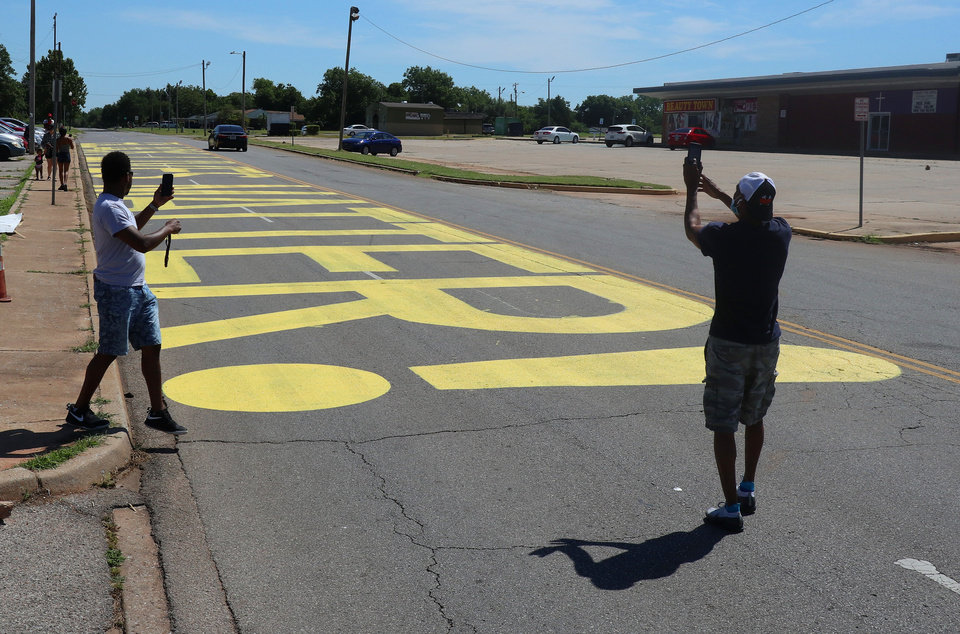 Photo - Two men take photos of the Black Lives Matter! that was painted on the west bound lanes of Springlake Dr., just east of the intersection of NE 36th and Kelley Ave.,Wednesday, June 24, 2020. [Doug Hoke/The Oklahoman]