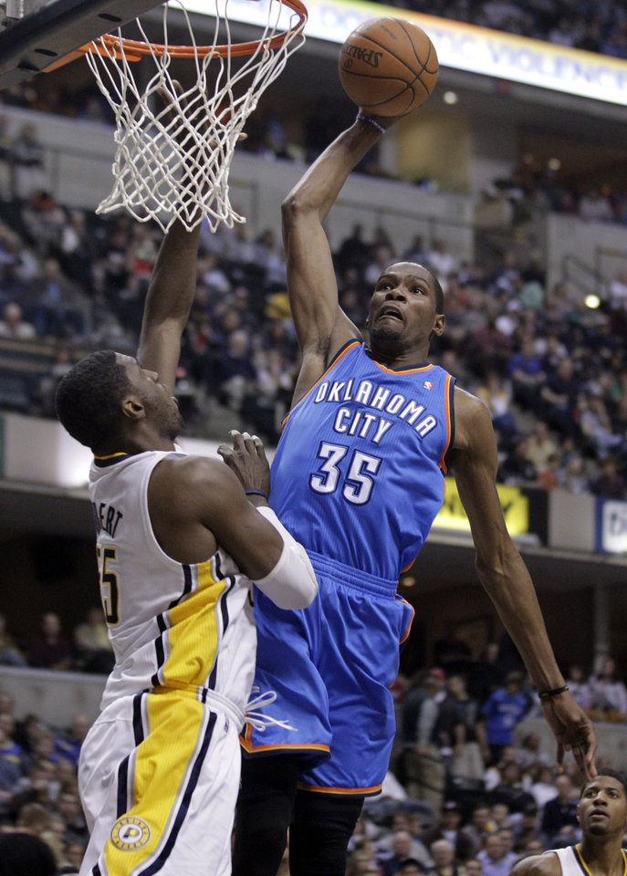 Photo - Oklahoma City Thunder forward Kevin Durant, right, goes up for a dunk over Indiana Pacers center Roy Hibbert in the first half of an NBA basketball game in Indianapolis, Friday, April 6, 2012.  (AP Photo/Michael Conroy) ORG XMIT: NAF102