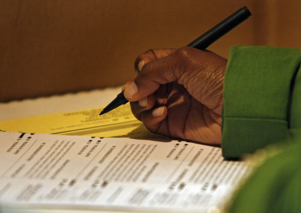 Photo - A voter fills out their ballot at the Presidential election polling location at Canadian Hills Church of the Nazarene on Tuesday, Nov. 4, 2008, in Yukon, Okla.   BY CHRIS LANDSBERGER, THE OKLAHOMAN
