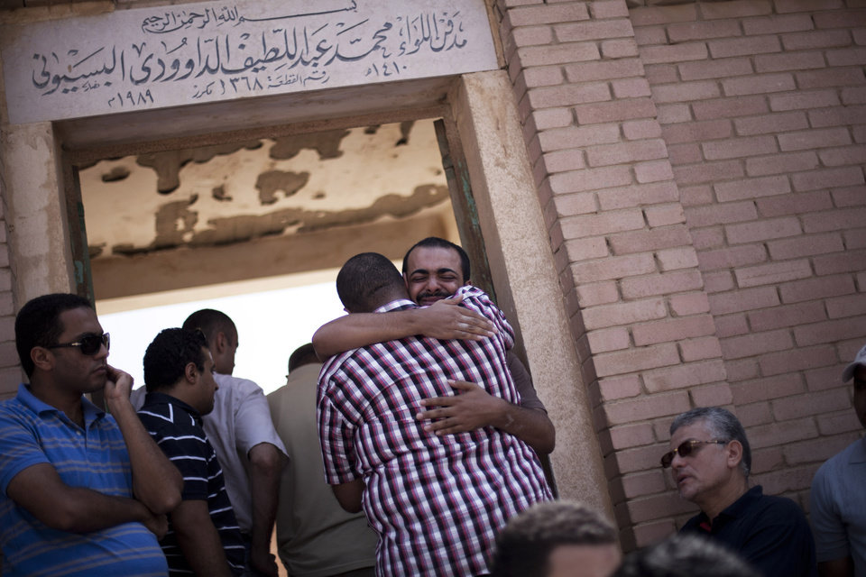 Photo - A friend of Ammar Badie, 38, killed Friday by Egyptian security forces during clashes in Ramses Square, and also son of Muslim Brotherhood's spiritual leader Mohammed Badie, comforts a relative while attending his burial in Cairo's Katameya district, Egypt, Sunday, Aug. 18, 2013. Egypt increased security at the Supreme Constitutional Court building ahead of planned mass rallies by supporters of the country's ousted President Mohammed Morsi. (AP Photo/Manu Brabo)