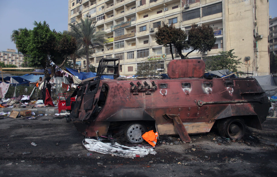 Photo - A burned army vehicle remains on a side street outside Rabaah al-Adawiya mosque, where supporters of Egypt's ousted President Mohammed Morsi had a protest camp at Nasr City, Cairo, Egypt, Thursday, Aug. 15, 2013. Egypt faced a new phase of uncertainty on Thursday after the bloodiest day since its Arab Spring began, with hundreds of people reported killed and thousands injured as police smashed two protest camps of supporters of the deposed Islamist president. Wednesday's raids touched off day-long street violence that prompted the military-backed interim leaders to impose a state of emergency and curfew, and drew widespread condemnation from the Muslim world and the West, including the United States. (AP Photo/Khalil Hamra)