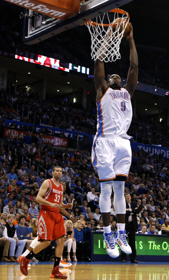 Photo - Oklahoma City's Serge Ibaka (9) dunks as Houston's Francisco Garcia (32) looks on during the NBA game between the Oklahoma City Thunder and Houston Rockets at the  Chesapeake Energy Arena  in Oklahoma City, Okla., Tuesday, March 11, 2014. Photo by Sarah Phipps, The Oklahoman