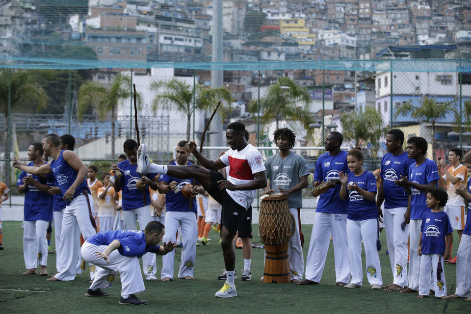 Photo - England national soccer team player Danny Welbeck, center, joins in a Capoeira dance demonstration with locals during a visit by a five England players to the Rocinha Sports Complex on the edge of the Rocina favela in Rio de Janeiro, Brazil, Monday June 9, 2014.  The England soccer team are staying in Rio de Janeiro as their base city for the 2014 soccer World Cup.  (AP Photo/Matt Dunham)