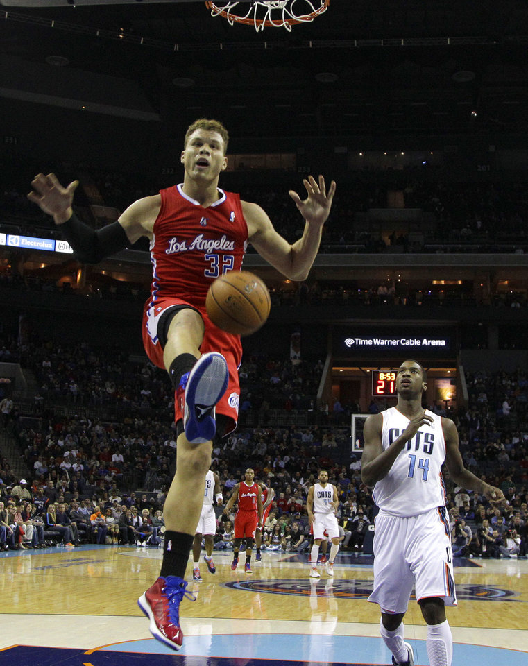 Photo - Los Angeles Clippers' Blake Griffin (32) reacts after dunking as Charlotte Bobcats' Michael Kidd-Gilchrist (14) look on during the first half of an NBA basketball game in Charlotte, N.C., Wednesday, Dec. 12, 2012. (AP Photo/Chuck Burton)