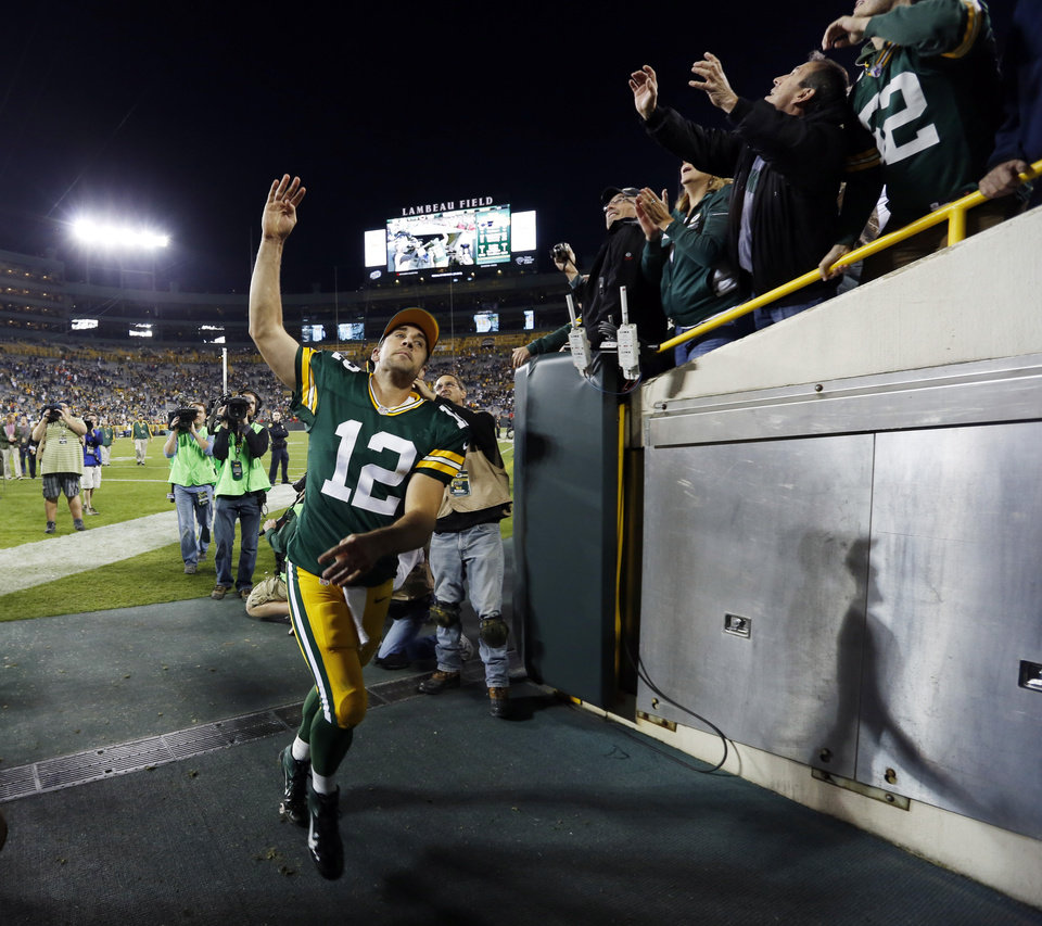 Photo -   Green Bay Packers' Aaron Rodgers tosses his wristbands to fans as he runs into the locker room after the second half of an NFL football game against the Chicago Bears Thursday, Sept. 13, 2012, in Green Bay, Wis. The Packers won 23-10. (AP Photo/Mike Roemer)