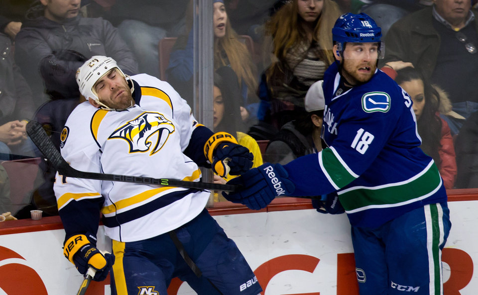 Photo - Nashville Predators' Eric Nystrom, left, is checked by Vancouver Canucks' Ryan Stanton during the second period of an NHL hockey game Wednesday, March 19, 2014. (AP Photo/The Canadian Press, Darryl Dyck)
