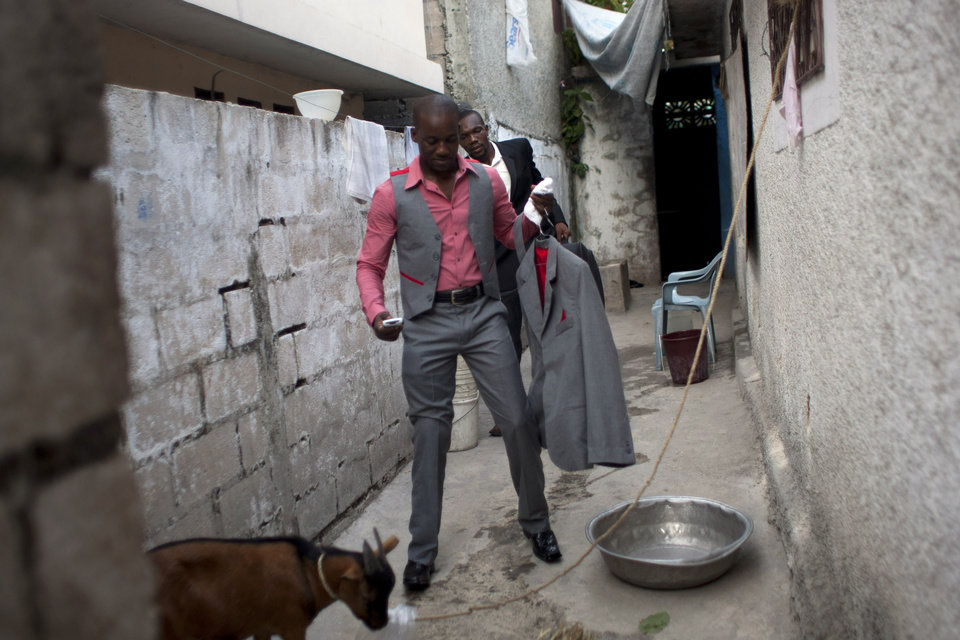 Photo - In this July 20, 2012 photo, professional dancer Georges Exantus walks out of his home to his wedding ceremony in Port-au-Prince, Haiti. Georges Exantus thought he'd never dance again. The earthquake three years ago in Haiti's capital flattened the apartment where he was living and he spent three days trapped under a heap of jagged rubble. After friends dug him out, doctors amputated his right leg just below the knee. Exantus walks with a slight limp and he can't dance as fast as he used to or balance as well or do some of his old moves, such as flipping his partner over his shoulder. (AP Photo/Dieu Nalio Chery)
