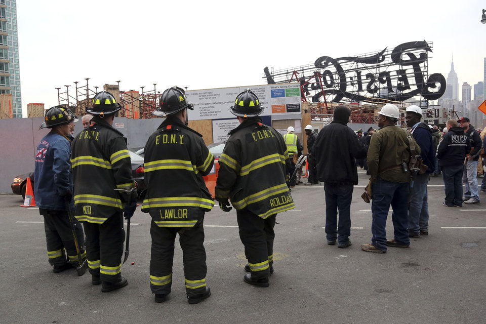 Photo - Firefighters, police officers and construction workers work the scene of a crane collapse at a construction site in the Queens borough of New York, Wednesday, Jan. 9, 2013, behind a big neon