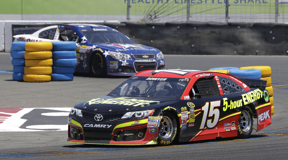 Photo - Clint Bowyer (15) leads Kevin Harvick during the NASCAR Sprint Cup Series auto race on Sunday, June 22, 2014, in Sonoma, Calif. (AP Photo/Eric Risberg)