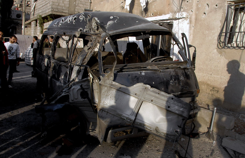 Photo -   This photo released by the Syrian official news agency SANA, shows Syrians standing near a damaged vehicle at the scene after an attack in Damascus, Syria, Wednesday, Nov. 7, 2012. (AP Photo/SANA)