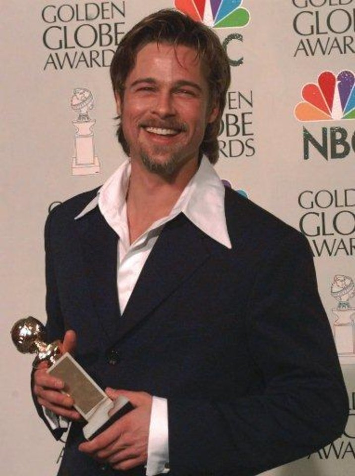 "Brad Pitt displays the award he received for best performance by an actor in a supporting role in a motion picture for ""12 Monkeys"" at the Golden Globe Awards, Sunday, Jan. 21, 1996, in Beverly Hills, Calif. (AP Photo/Mark J. Terrill)"