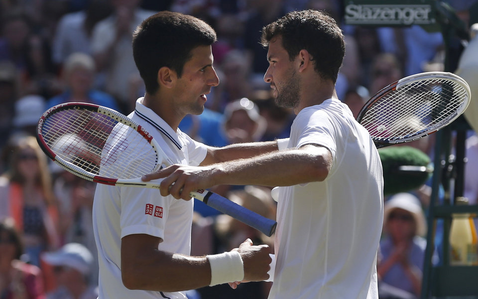Photo - Novak Djokovic of Serbia, left, shakes hands with Grigor Dimitrov of Bulgaria after he defeated him in their men's singles semifinal match at the All England Lawn Tennis Championships in Wimbledon, London, Friday, July 4, 2014. (AP Photo/Pavel Golovkin)
