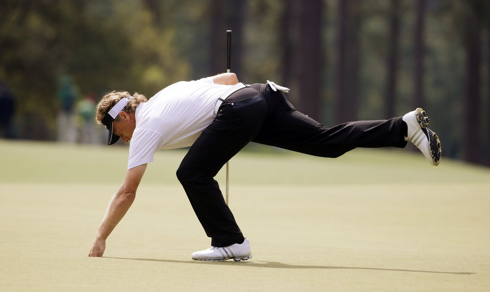 Photo - Bernhard Langer, of Germany, gets his ball out of the cup after putting on the eighth green during the second round of the Masters golf tournament Friday, April 11, 2014, in Augusta, Ga. (AP Photo/Darron Cummings)
