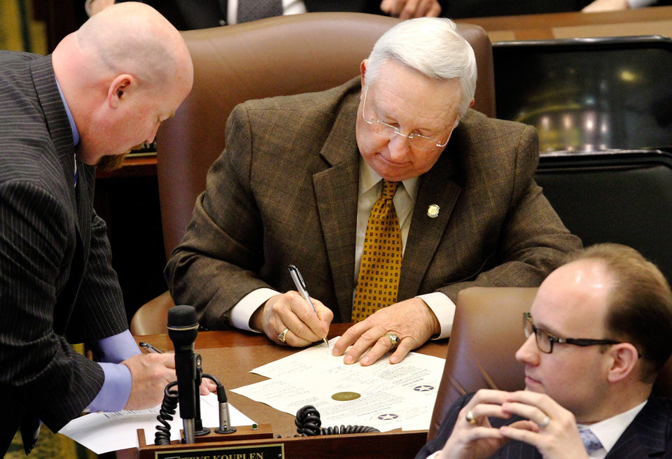 Photo - Reps. Joe Dorman, left, and Steve Kouplen sign documents at their desks before Gov. Mary Fallin delivers her 2012 State of the State address to a joint session of the Oklahoma legislature in the House Chamber on the opening day of the session, Monday, Feb, 6, 2012.  At lower right is Rep. Scott Inman.  Photo by Jim Beckel, The Oklahoman
