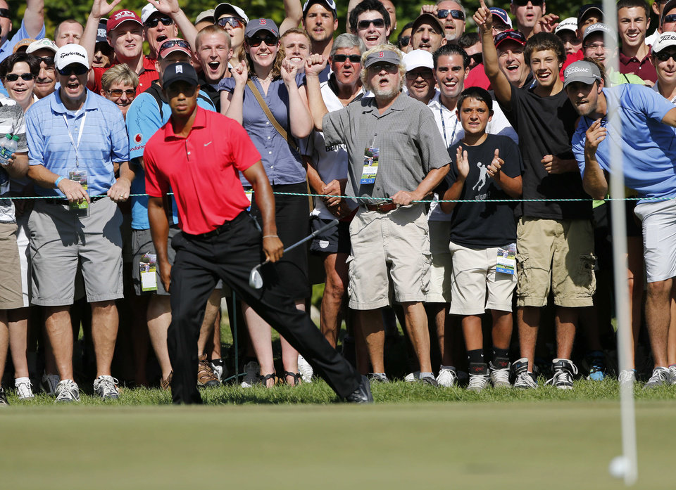 Photo -   Tiger Woods, foreground left, reacts after his chip onto the green failed to drop into the hole on the seventh green during the final round of the Deutsche Bank Championship PGA golf tournament at TPC Boston in Norton, Mass., Monday, Sept. 3, 2012. (AP Photo/Michael Dwyer)